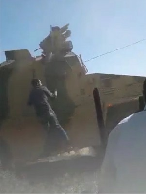 a_civilian_barehanded_protestor_tries_to_get_on_a_turkish_military_vehicle_which_drives_off_obs._av__ef_scr.shot_400